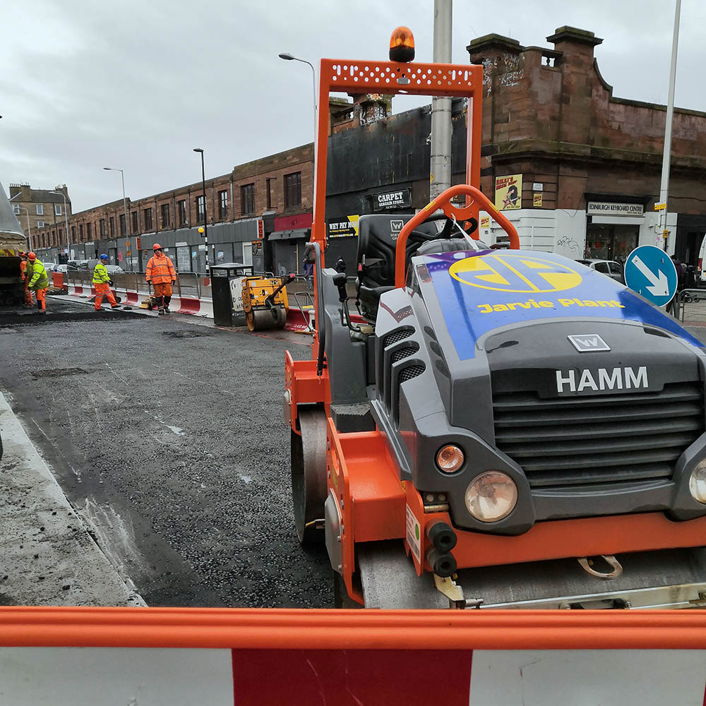 Close up of tarmac rolling moving vehicles with construction workers