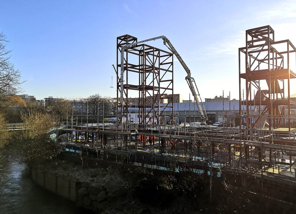 Wide shot of construction yard with crane building houses, with potential for falls from heights