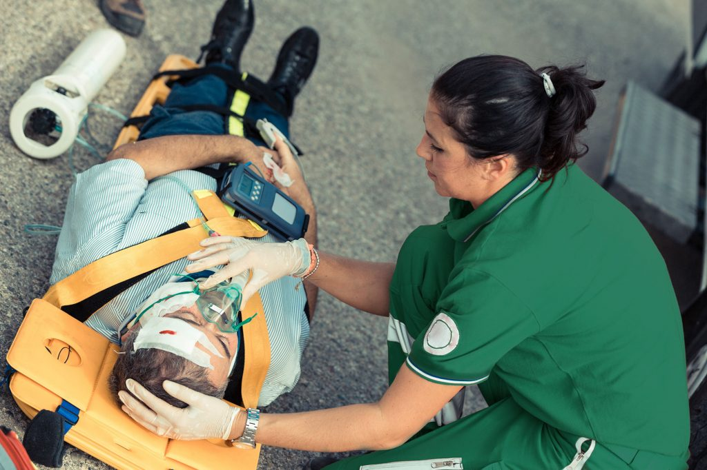 Paramedic saving a life after an accident, healthcare and medical workers