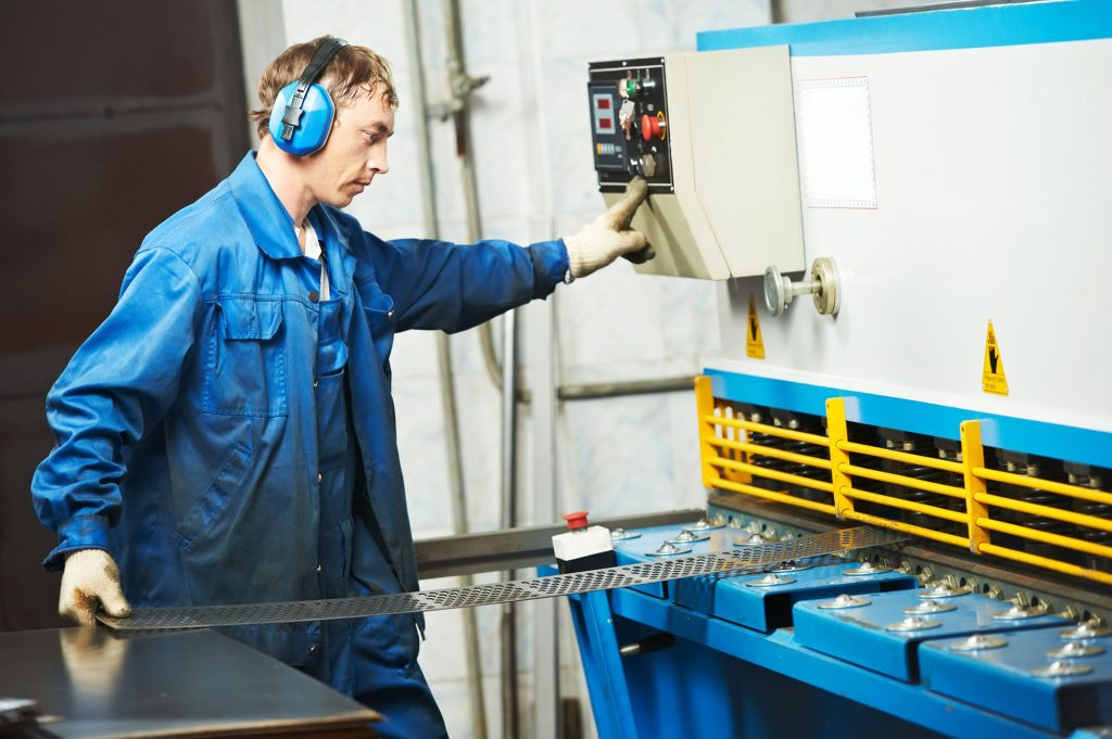 Manufacturing worker using moving machine to cut sheet metal