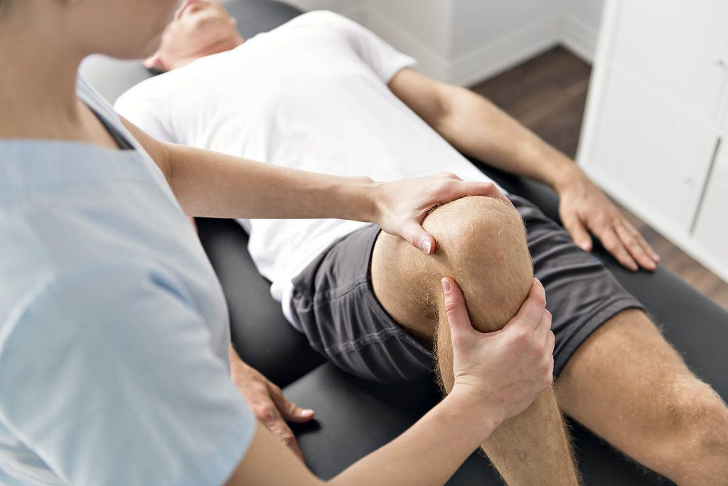 Physiotherapist working with patient who has musculoskeletal disorder in their knee