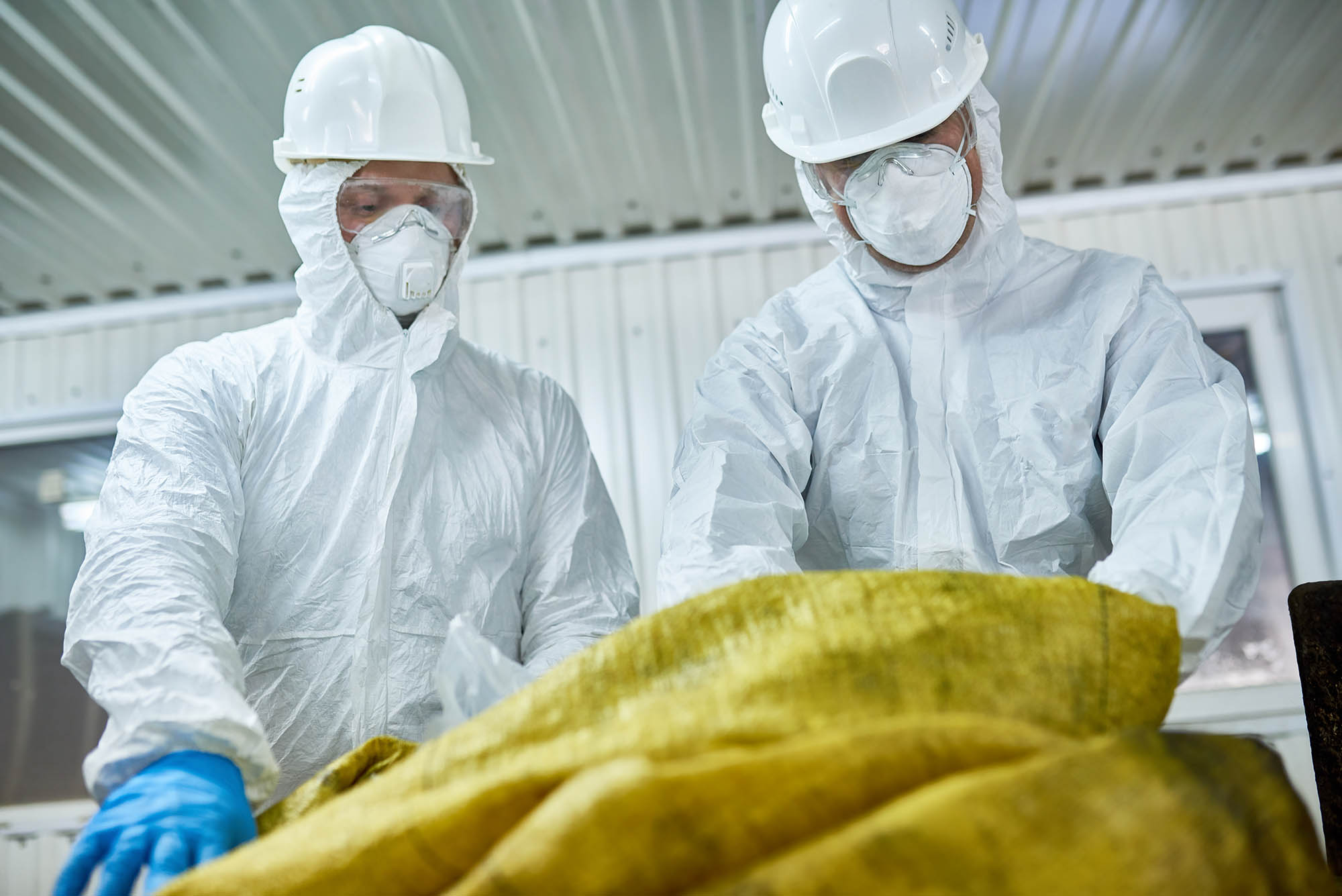 Waste management workers wearing biohazard suits working at waste processing plant sorting recyclable materials, work-related illness protection