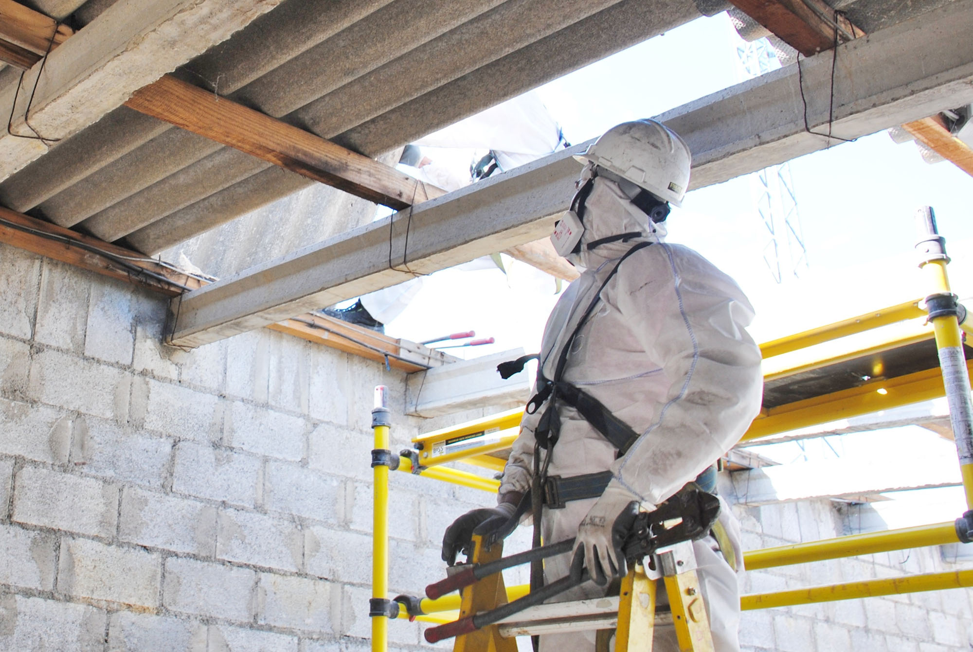 Construction worker handling asbestos removal in a building with PPE